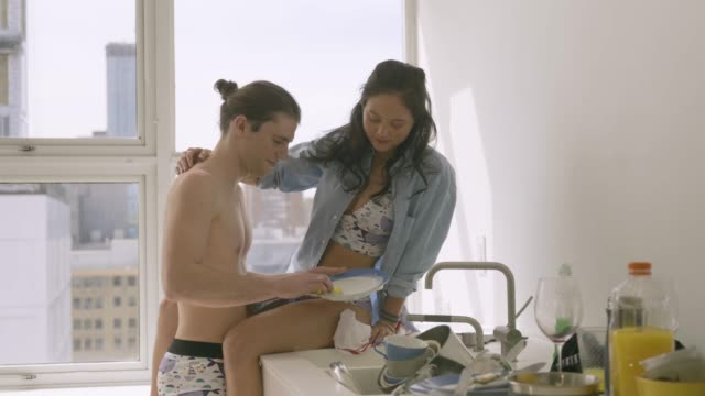 young couple having fun in modern kitchen. - washing up stock videos & royalty-free footage