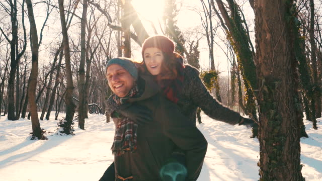 young couple having fun in winter season. - piggyback stock videos & royalty-free footage