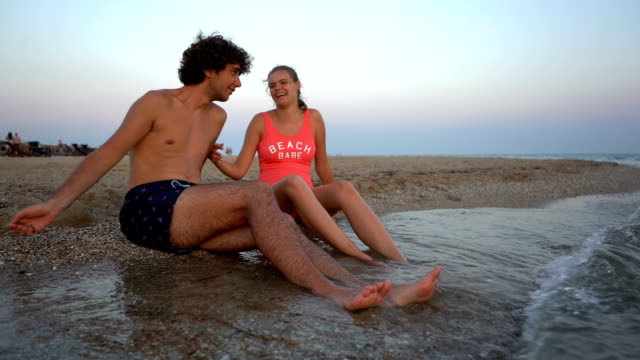 vídeos de stock e filmes b-roll de young couple having fun on beach - swimwear