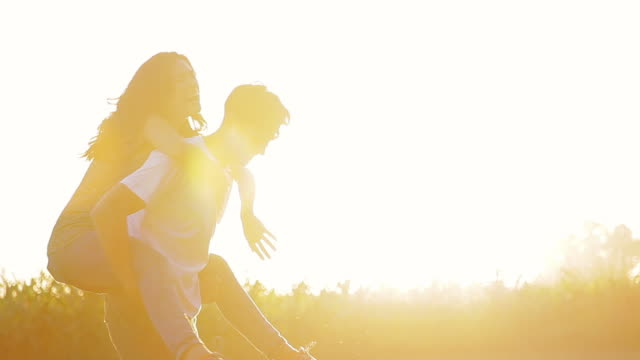 Young couple having fun together outdoors, backlit by golden sunlight