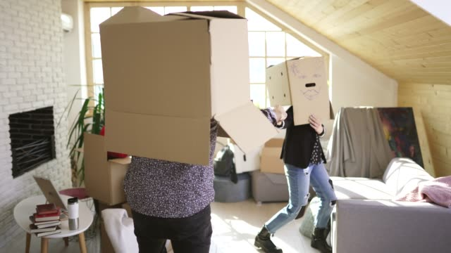young couple having fun with cardboard boxes in new apartment - unpacking stock videos & royalty-free footage