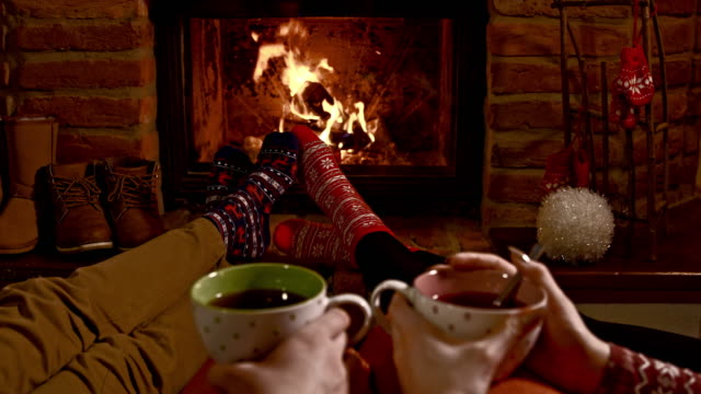 ds r/f young couple having hot tea by the fireplace - sock stock videos & royalty-free footage