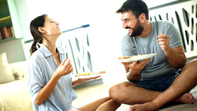 young couple having lunch on the living room floor. - cross legged stock videos & royalty-free footage