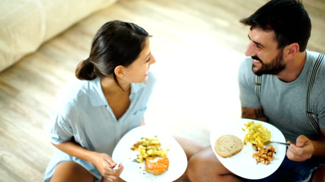 young couple having lunch on the living room floor. - sitting on ground stock videos & royalty-free footage