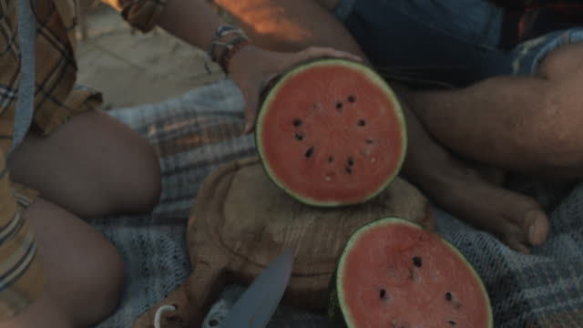 vídeos de stock, filmes e b-roll de young couple having picnic, cutting water melon on picnic blanket and wooden board in the sand dunes at the atlantic beach in the south of france - corte transversal