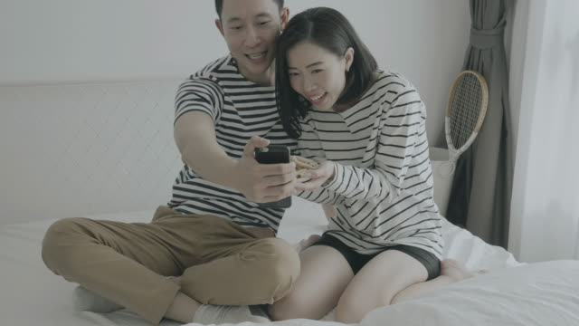 Young couple having snack while using smartphone at home, enjoying their love and marriage while eating, talking and showing to friend in social network - social media concept