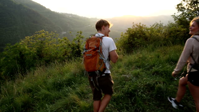 Young couple hike through meadow with backpacks at sunrise