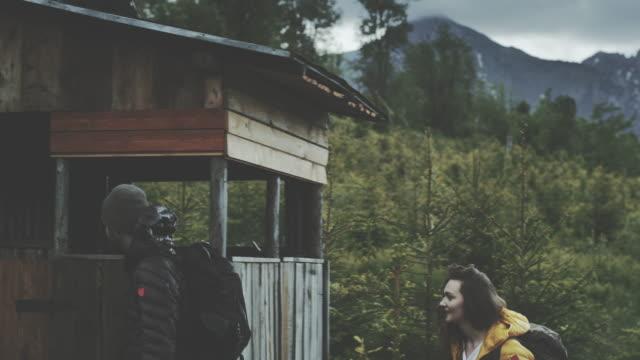 vídeos de stock e filmes b-roll de young couple hiking in the mountains. cabin in the background - cabana de madeira