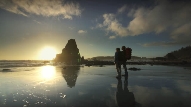 stockvideo's en b-roll-footage met young couple hiking on pacific ocean beach at sunset - oregon amerikaanse staat