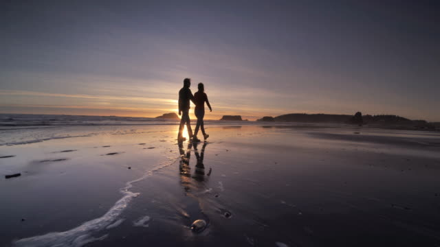 Young couple hiking on Pacific Ocean Beach at Sunset