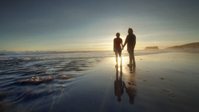 young couple hiking on pacific ocean beach at sunset - idylle stock-videos und b-roll-filmmaterial