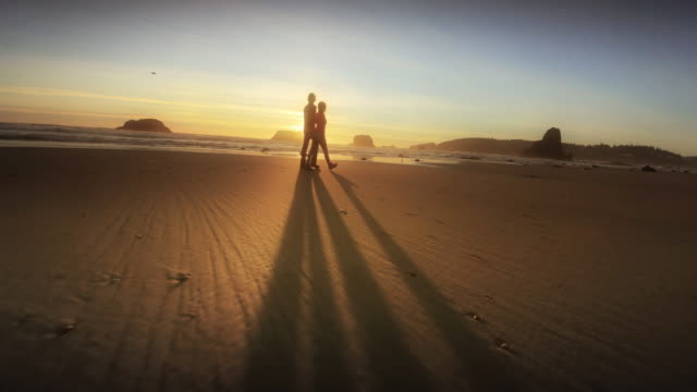 young couple hiking on pacific ocean beach at sunset - oregon coast stock videos & royalty-free footage