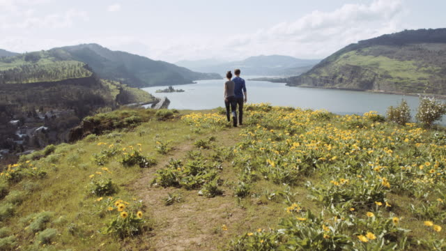 young couple hiking to cliff viewpoint - columbia river gorge stock videos & royalty-free footage