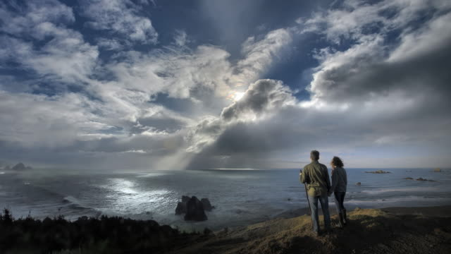 Young couple hiking to view of storm over Pacific Ocean at sunset, Oregon