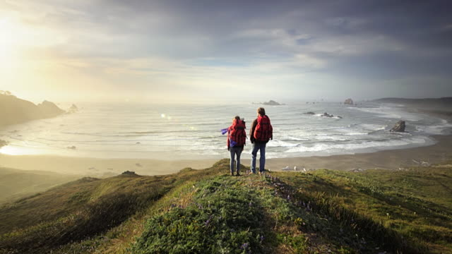 young couple hiking trail overlooking pacific ocean, oregon - horizon stock-videos und b-roll-filmmaterial