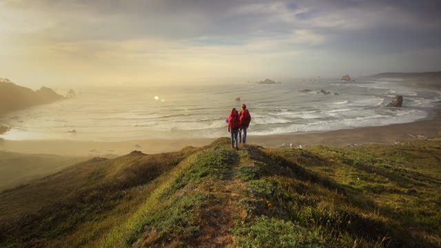 Young couple hiking trail overlooking Pacific ocean, Oregon