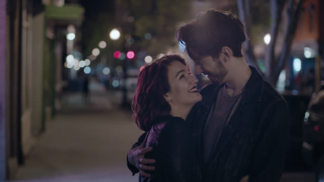 MS SLO MO. Young couple hold each other and smile on city sidewalk at night.