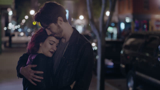 MS SLO MO. Young couple hold each other on city sidewalk at night.
