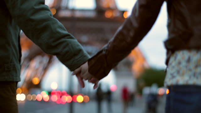 HANDHELD CLOSE UP REAR TRACKING SHOT young man and woman hold hands while walking toward Eiffel Tower in Paris at dusk