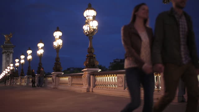 A couple hold hands while walking along the Alexander Bridge.