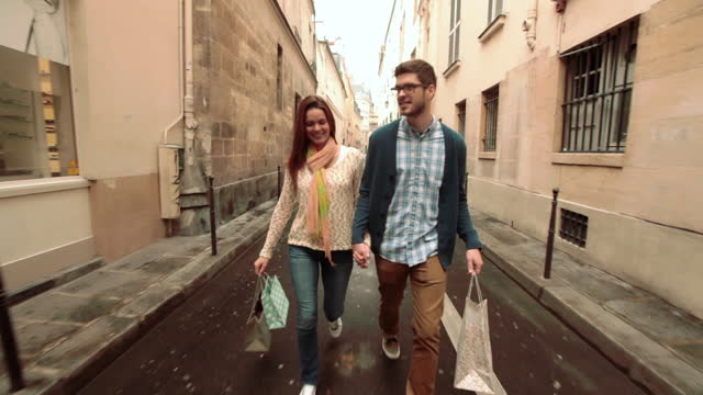 Young couple hold hands as they walk and talk down a side street on a shopping trip in Paris.