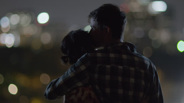 Young couple hold hands, embrace, and kiss overlooking a city skyline