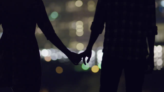 vídeos de stock e filmes b-roll de young couple hold hands overlooking a city skyline - par