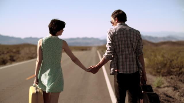 vídeos y material grabado en eventos de stock de young couple hold hands walking down a lonely desert road - maleta