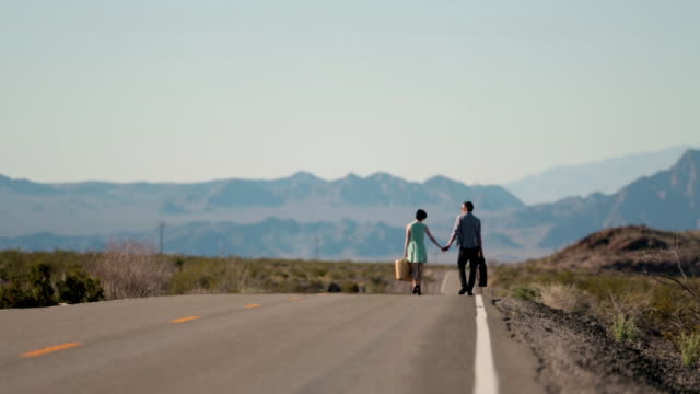 Young couple hold hands walking down a lonely desert road