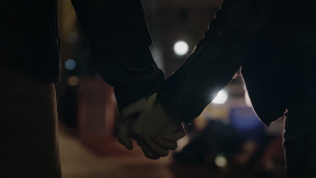 CU SLO MO. Young couple hold hands walking through city at night.