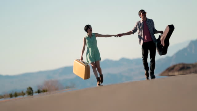 Young couple hold hands walking up a lonely desert road