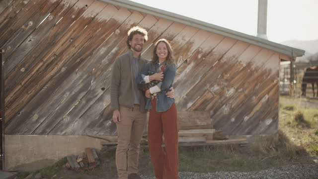 young couple holding a chicken in front of a barn - girlfriend stock videos & royalty-free footage