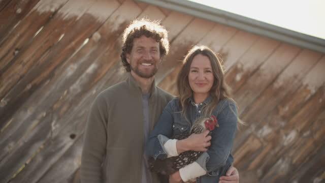 young couple holding a chicken in front of a barn - byggnadskonstruktion bildbanksvideor och videomaterial från bakom kulisserna