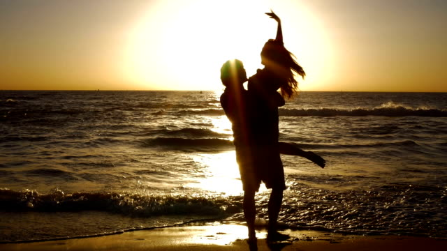 young couple holding hands and spinning on beautiful ocean beach at sunset. - lift stock videos & royalty-free footage