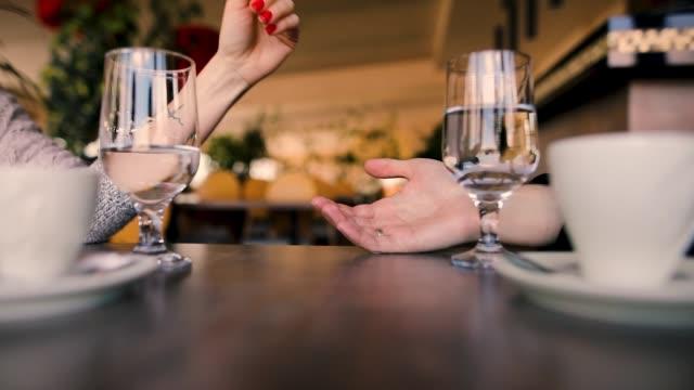 レストランに座っている間、デートの夜に手をつないでいる若いカップル - お食事デート点の映像素材/bロール