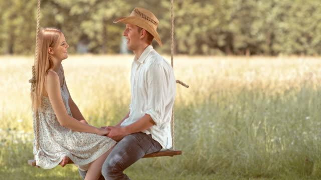 SLO, dans le Missouri, ma jeune couple sur une balançoire dans la campagne