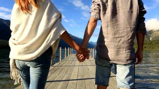 Young couple holding hands on lake pier