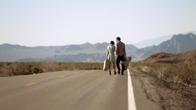 young couple holding hands stop to embrace on a lonely desert road - ヒッチハイキング点の映像素材/bロール