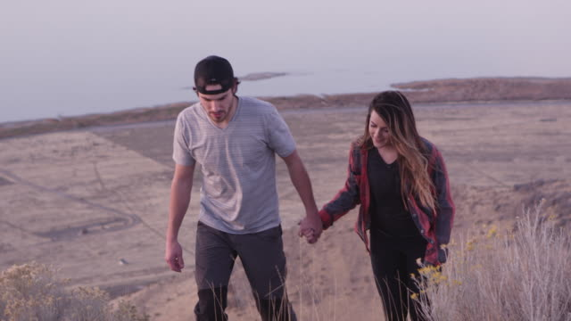young couple holding hands while hiking - fully unbuttoned stock videos & royalty-free footage