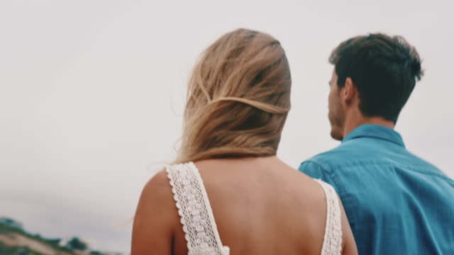 young couple holding hands while walking at beach - boyfriend stock videos & royalty-free footage