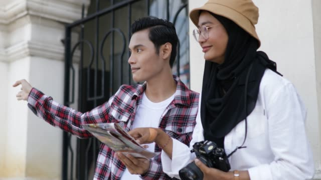 young couple holding map and sightseeing in town - merdeka square kuala lumpur stock videos & royalty-free footage