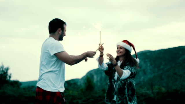vídeos de stock e filmes b-roll de young couple holding sparklers and dancing - chapéu do pai natal