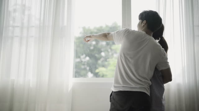 young couple hug and talking at window in the morning. - window frame stock videos and b-roll footage