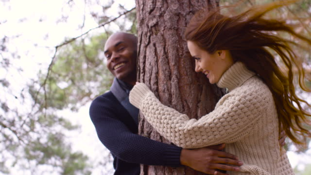 a young couple hugging a tree during a forest walk in autumn - rufsig bildbanksvideor och videomaterial från bakom kulisserna