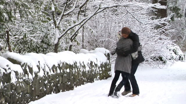 SLO MO WS Young couple hugging in snowy park, Vancouver, British Columbia, Canada