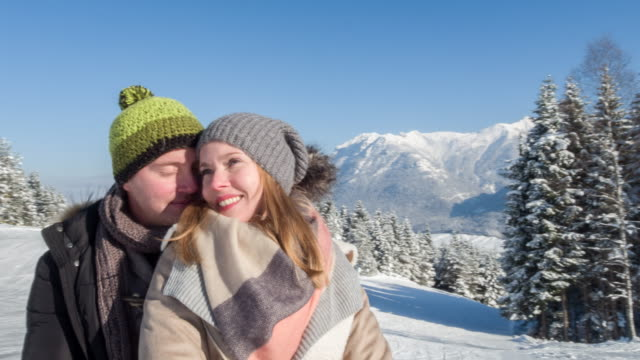 Young couple hugging in winter landscape, Bavarian Alps