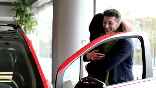 Young couple in a car dealership