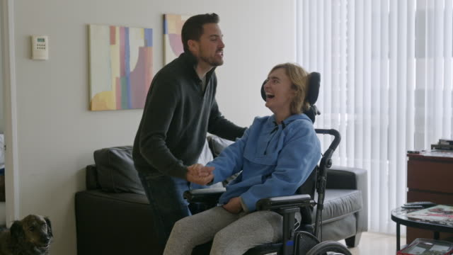 vidéos et rushes de young couple in apartment living room, woman is in a wheelchair. - chaise roulante