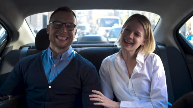 young couple in back seat at car happily talking, daytime - passenger seat stock videos & royalty-free footage