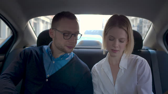 young couple in back seat at car, looking at phone, daytime - passenger seat stock videos & royalty-free footage